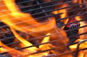 stock photo of barbie  - Just lighting the barbecue and the flames are coming up through the grill - JPG