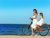 stock photo of mother child  - mother and daughter riding a bike  on the beach - JPG