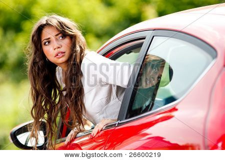 Young pretty woman looking at back of car