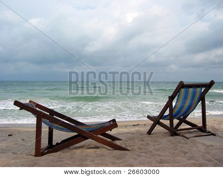 Two empty beach chairs overlook stormy sea. Samui, Thailand