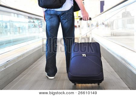 Traveler with a suitcase on the speedwalk