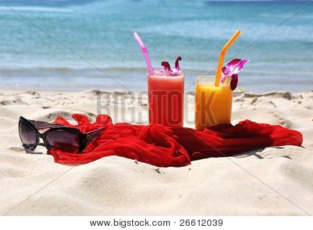 Pair of fruit shakes, red shawl and sunglasses on the tropical beach