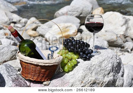 Red wine and grapes served at a picnic. Verzasca valley, Switzerland