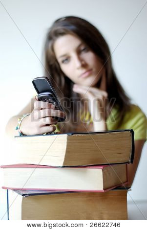 Girl student calls with cellular and pile of book
