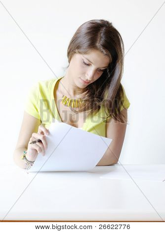 Girl student writes the exercise of the examinations paper