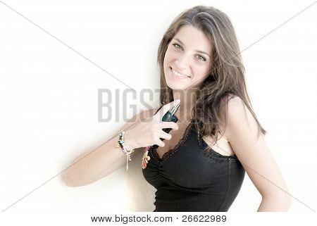 Smiling girl spray the perfume of a bottle