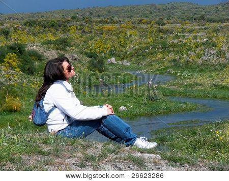 girl resting on the grass near the snake path of creek
