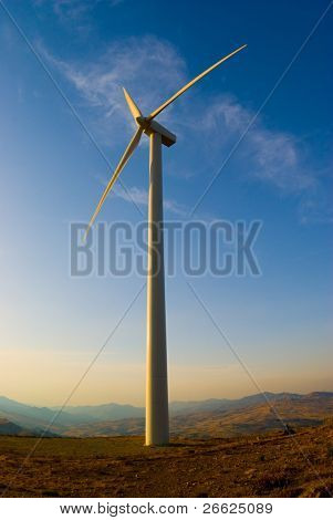 single wind turbine in sunset