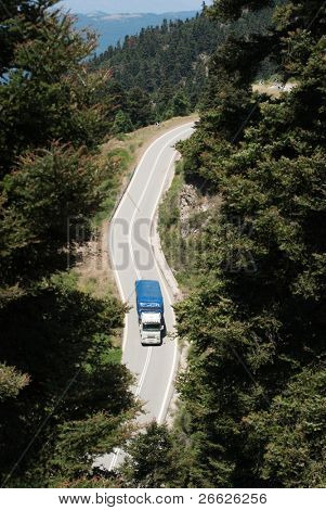 aerial view of truck crossing a forest of a mountain road