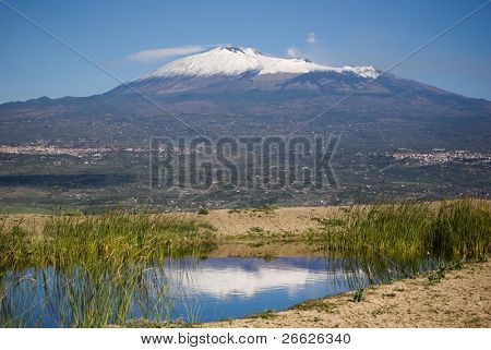 wide view of the imposing Mount Etna partially covered with snow and it is reflected in a pond