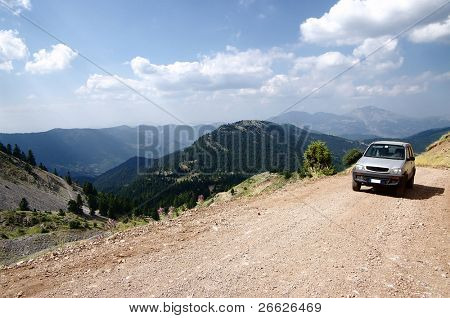 aerial view for vehicle off-road on dirty road of greek mountain
