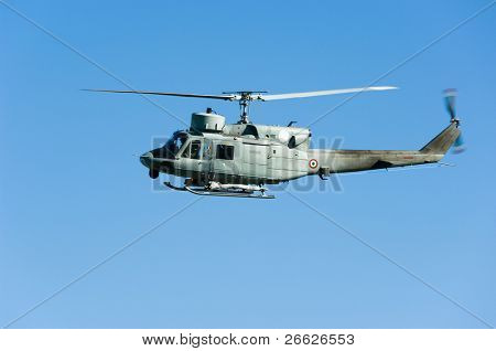 military helicopter flying in the blue sky