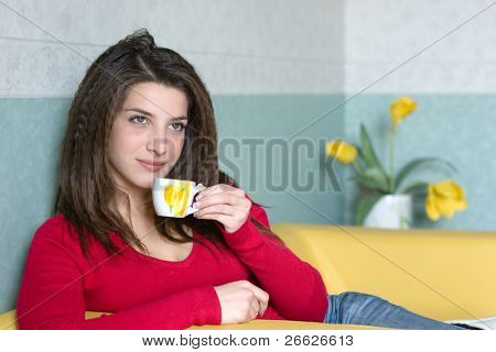 a pretty girl takes a break sipping a coffee on the yellow sofa