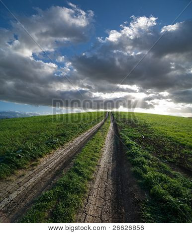 dirt road leading on top of the hill covered by the lush grass, on background the sun is setting between stormy clouds
