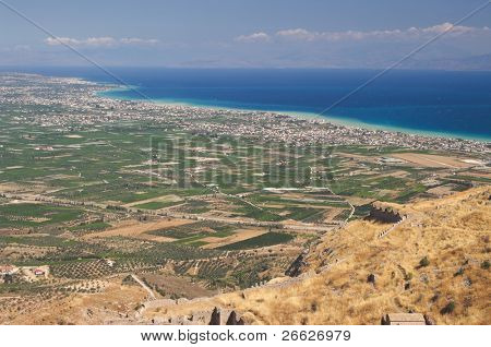 aerial view on the cultivated land and on the suburbs urban along marine coast of gulf of Corinth from the rock of Acrocorinth in Greece