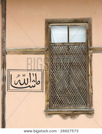 arabic calligraphy and typical wooden window on facade of ottoman house style in Safranbolu, Turkey