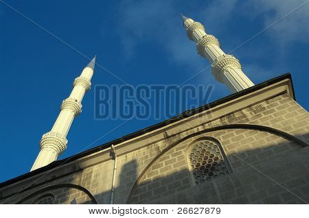below view of minarets of mosque against blue sky in Levent neighborhood, Istanbul, Turkey