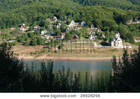 chalet and church on Mavrovo lakefront in the republic of Macedonia