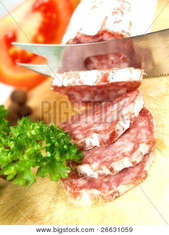 Salami slices with cutting knife