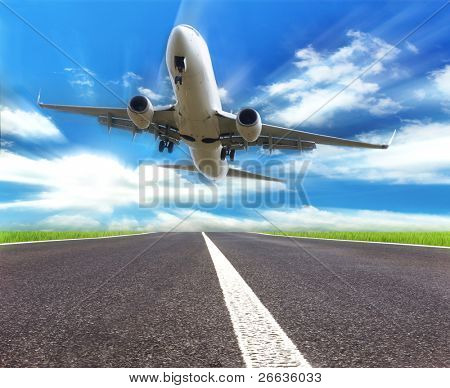 Airplane landing on runway with sunrays on background