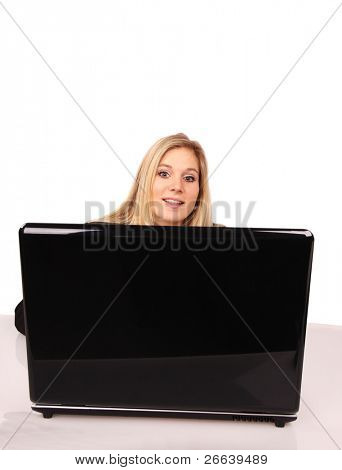Beautiful blond girl behind laptop