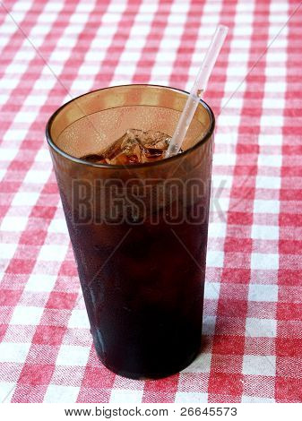 Dark glass with a straw on red and white tablecloth