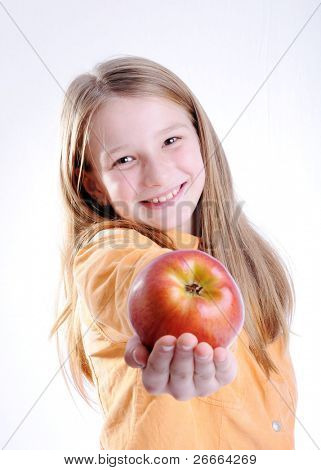 Child is smiling and holding a red apple. Isolated on white background