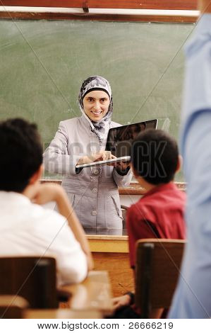 Arabic female teacher in classroom showing a laptop to children and smiling