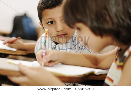 Positive cute kid in the school, writing on table, red apple in front of him