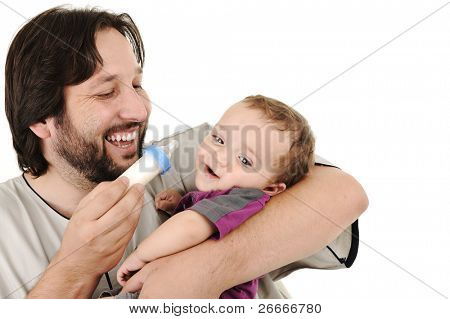 Young father trying to feed his little baby son in arms