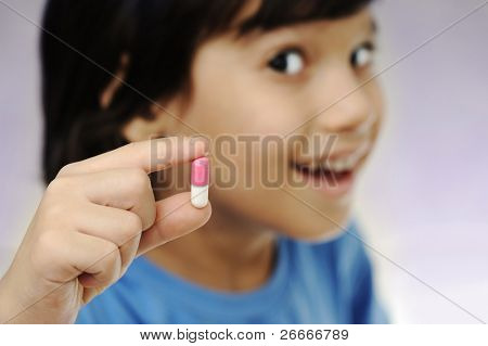 Happy boy with pill in hand smiling