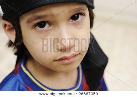sad cry kid boy is looking at camera