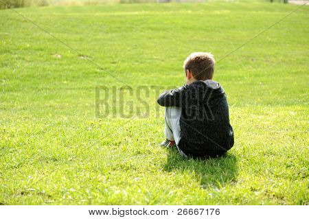 Sad abandoned orphan sitting in nature and contemplating, autism syndrome