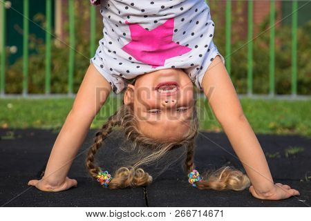 poster of Little Girl Stands On Her Hands And Smiles. Child Has Fun Outside. Kid Enjoys Upside Down. Exercises