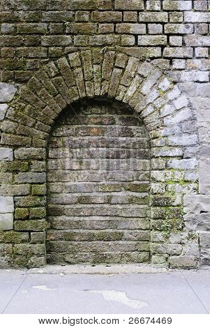 Archway in a brick stone wall