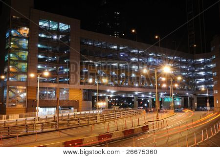A lit parking garage in the city.