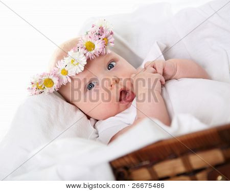 Portrait of a baby girl with a wreath of flowers