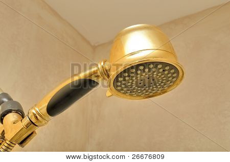 A golden shower head in a shower