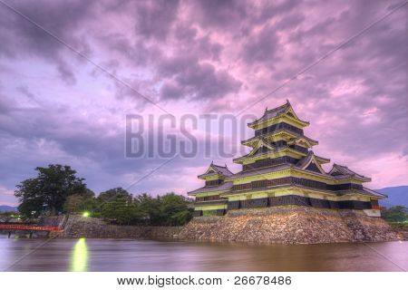 The historic Matsumoto Castle under pink skies, dating from the 15th Century in Matsumoto, Japan.