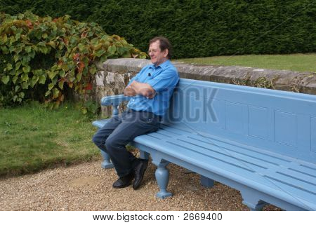 A Man Crossing His Arms And Legs Sitting Relaxing On A Bench In A Garden