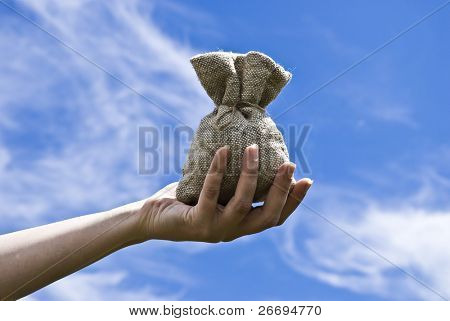 Hand with sack on background sky