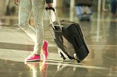Black Travel Bag Or Suitcase On Wheels In Hand And Female Legs In Floral Jeans And Bright Pink Gumsh poster