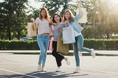 Group Of Young Asian Woman Shopping In An Outdoor Market With Shopping Bags In Their Hands. Young As poster