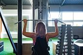 Young Fit Woman At The Gym Doing Pulldown Exercise With Weight Machine. Female Athlete At A Fitness  poster