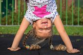 Little Girl Stands On Her Hands And Smiles. Child Has Fun Outside. Kid Enjoys Upside Down. Exercises poster