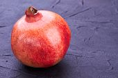 Whole Unpeeled Pomegranate On Dark Background. Ripe Organic Pomegranate On Black Textured Surface Wi poster