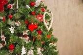 Christmas Tree Over Beige Wall.colorful Christmas Decorations Hanging From The Branches Of The Chris poster