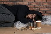 Poor Homeless Man Lying On Floor Near Brick Wall poster