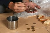 Poor Man Counting Coins Over Cardboard On Floor, Closeup poster