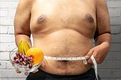 Fat Man Diet With Fruit Using Measuring Tape To Measuring His Stomach At Home. Fat Man Diet poster